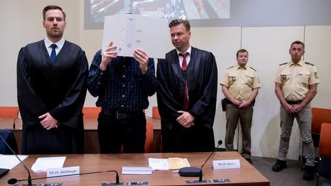 Der Angeklagte Philipp K. aus Marburg steht im Münchener Landgericht zwischen seinen Anwälten. Sein Gesicht hat er mit einem Aktenordner verdeckt.