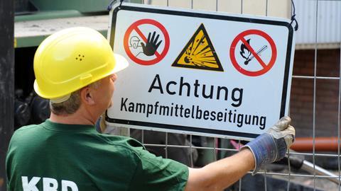 """Ein Mann mit Helm hängt ein Schild mit der Aufschrift """"Achtung Kampfmittelbeseitigung"""" an einen Zaun"""