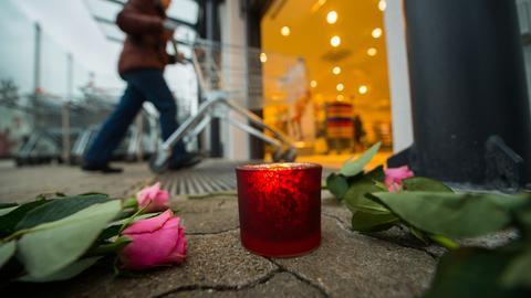 Kerze und Blume auf dem Pflaster.