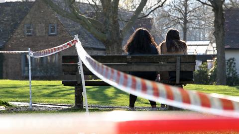 Zwei junge Frauen sitzen auf einer Parkbank neben einem abgesperrten Spielplatz.
