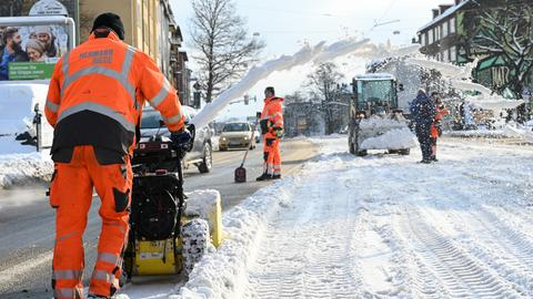 Mitarbeiter einer Baufirma räumen die Schneemengen von den Straßenbahngleisen.