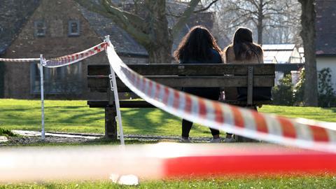 Zwei Teenie-Mädchen sitzen auf einer Parkbank neben einem abgesperrten Spielplatz nahe beieinander in der Sonne.