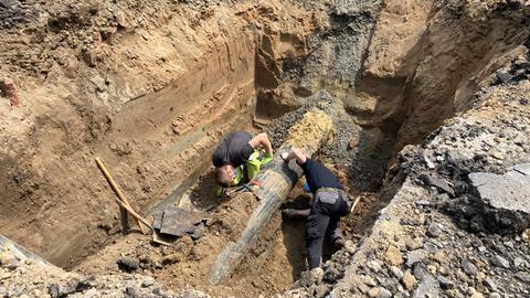 Zwei Arbeiter begutachten eine freigegrabene Gasleitung