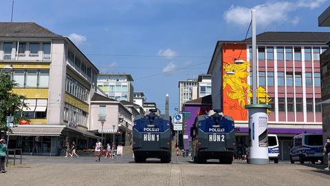 Zwei Wasserwerfer stehen am Friedrichsplatz in Kassel. Im Hintergrund ist die Fußgängerzone zu sehen.