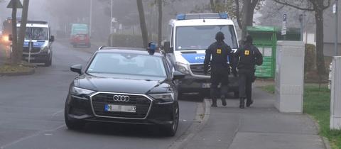 2 Polizisten und zwei Autos der Polizei in einer nebeligen Straße.