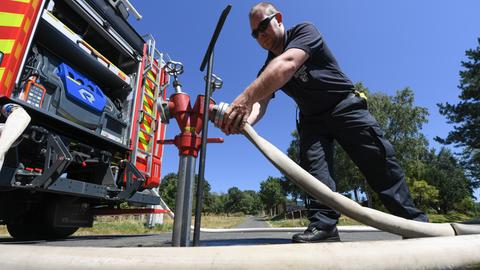 Ein Feuerwehrmann richtet eine Notleitung für Trinkwasser in Kelkheim ein.