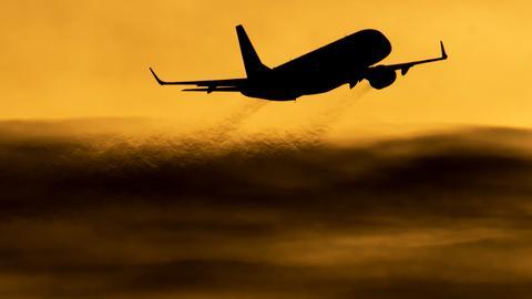 Die Silhouette eines startenden Flugzeugs.