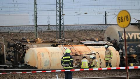 Feuerwehrleute arbeiten an dem Kesselwagen, der auf den Schienen liegt.