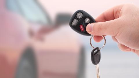 Eine Hand hält einen so genannten Keyless-Go-Schlüssel vor einem Auto