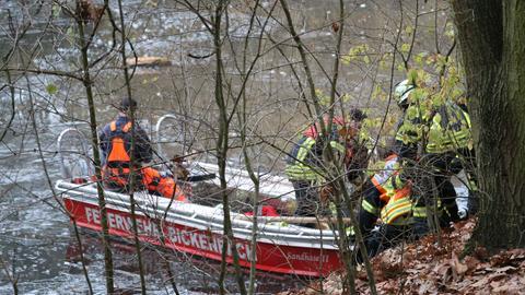 """Ein Boot mit der Aufschrift """"Feuerwehr Bickenbach"""" liegt am Rand eines Weihers. Feuerwehrleute stehen dabei."""