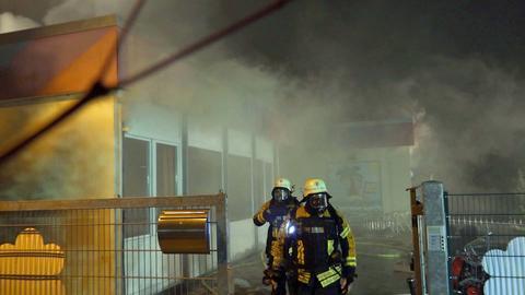 Feuerwehrleute am Kindergarten in Neckarsteinach, aus dem Rauch steigt.