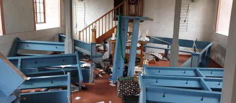 Umgeworfene Bänke in einer Kirche.