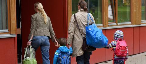 Eltern und Kinder vor einer Kita