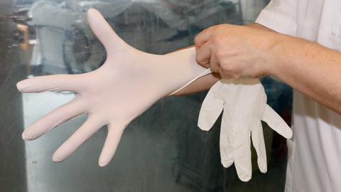 Ein Pfleger zieht Plastikhandschuhe an, im Hintergrund ein Intensiv-Bett.