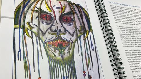 Eine Zeichnung zeigt eine monsterhafte Fratze.