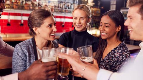 Mehrere Menschen stoßen mit ihren Biergläsern an.