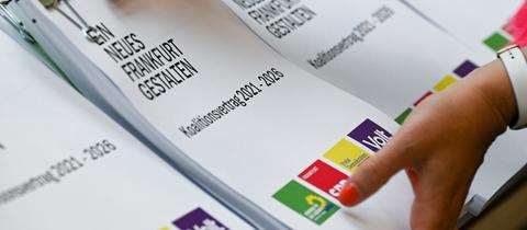 Frauenhände mit lackierten Fingernägeln halten den Koalitionsvertrag Frankfurt 2021