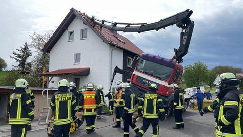 Feuerwehrleute sichern einen gekippten Baukran, dessen Ausleger auf ein Hausdach gestürzt ist.