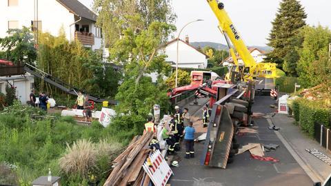 Der umgekippte Laster mit dem Kranarm auf dem Anbau auf der Straße. Menschen und Feuerwehreinsatzkräfte bewegen sich im Umfeld.