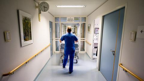 Schwester schiebt einen Patienten durch den Gang eines Krankenhauses
