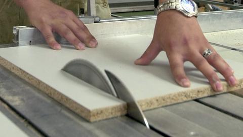 Eine Kreissäge und daneben zwei Hände, die ein Holz halten.