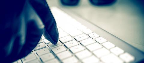 Eine Hand mit Handschuh tippt auf einer Computertastatur