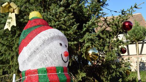 Künstlicher Schneemann mit roter Mütze vor geschmückter Tanne