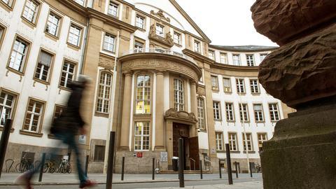 Das Land- und Amtsgericht Frankfurt von der Straße aus fotografiert. Davor ist ein Mensch zu sehen, wie er vorbeiläuft. Die Tür zum Gebäude steht offen.