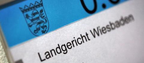 Eine Hinweistafel an einem Sitzungssaal im Landgericht Wiesbaden.
