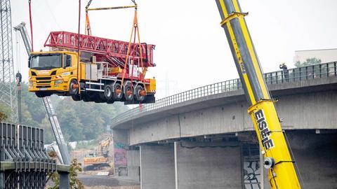 Ein Kran hebt einen Lastwagen durch die Luft, daneben die Salzbachtalbrücke.
