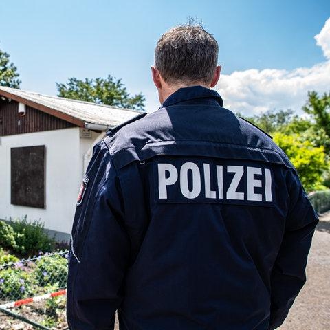 Polizist steht vor abgesperrter Laube