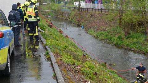 Feuerwehrleute bergen eine Leiche aus dem Flüsschen Dietzhölze in Dillenburg