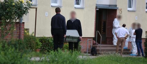 Ermittler tragen Sarg aus Wohnung.