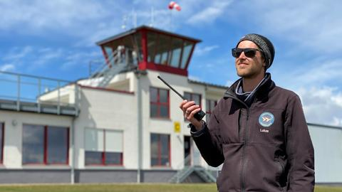 Der Leiter der auf der Flugschule Wasserkuppe, Lukas Schmidt-Nentwig, hält ein Funkgerät in der Hand.