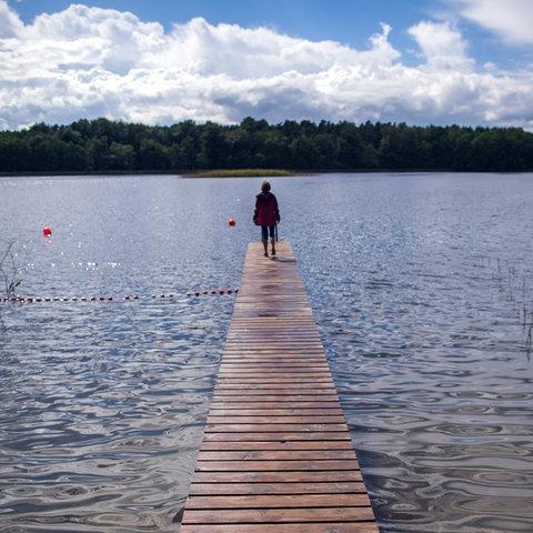 Eine Frau steht auf einem Steg am Leppinsee