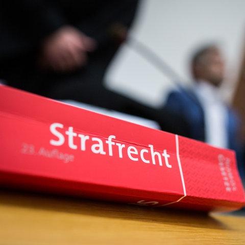 """Ein Buch mit dem Titel """"Strafrecht"""" liegt im Landgericht Gießen auf dem Tisch vor der Anklagebank."""