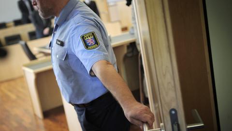 Ein Justizbeamter vom Landgericht Limburg schließt die Tür zum Verhandlungsraum.