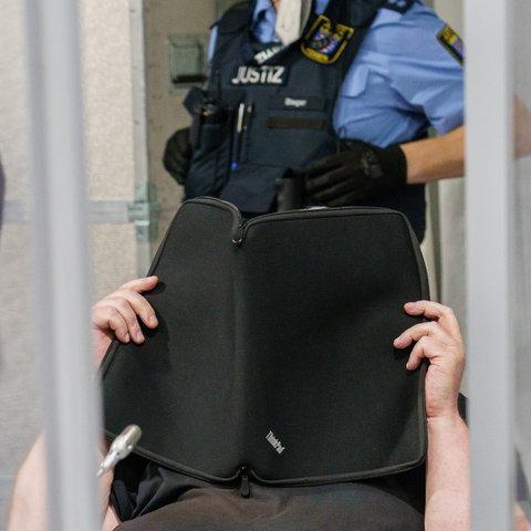 Ein Mann verdeckt sein Gesicht mit einer schwarzen Computerschutzhülle.