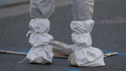 Eine Mitarbeiterin der Spurensicherung dokumentiert einen Schuh, der nach der Tötung einer Frau in der Innenstadt auf der Straße liegt.