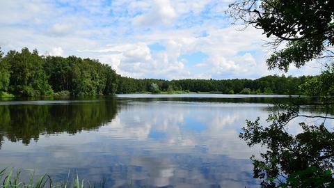 Blick auf einen See, in dem sich Wolken spiegeln