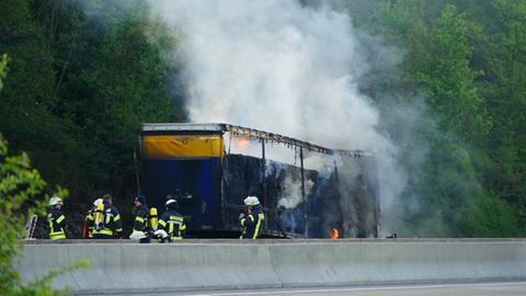 Feuerwehrleute beim Löschen des brennenden Lkw