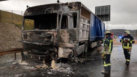 Feuerwehrleute stehen neben ausgebranntem Lkw auf der A4
