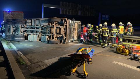 Ein Lkw-Fahrerhaus liegt umgestürzt auf der Fahrbahn. Etwa zehn Feuerwehrleute stehen davor.