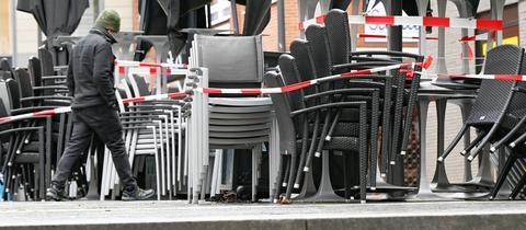 Gestapelte und abgeschlossene Sitzgelegenheiten vor einem gastronomischen Betrieb. Dazwischen läuft ein Mann in Winterkleidung mit geneigtem Kopf.