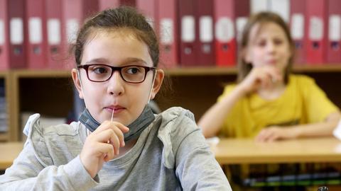 Grundschülerin führt im Klassenraum einen Lolli-Test (Teststäbchen im Mund) durch.