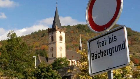 """Ein Schild """"Einfahrt verboten"""", darunter der Zusatz """"frei bis Bächergrund"""". Im Hintergrund der Kirchturm des Ortes."""