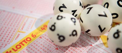 Lottokugeln liegen auf einem Tippschein.