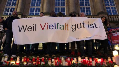 """Menschen tragen bei der Gedenkfeier in Kassel ein Banner mit der Aufschrift """"Weil Vielfalt gut ist."""""""