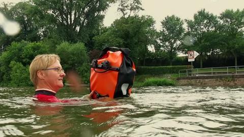 Mit der wasserdichten Packtasche durch den Main: Jutta Maaßen schwimmt zur Arbeit.