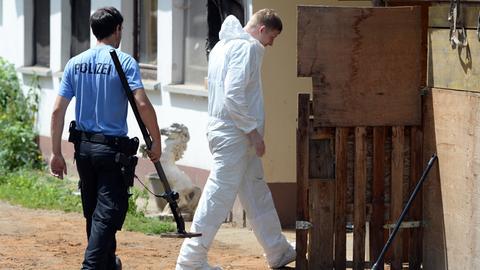 Ein Polizist mit einem Metalldetektor, ein Mann mit weißem Overall der Sprurensicherung.